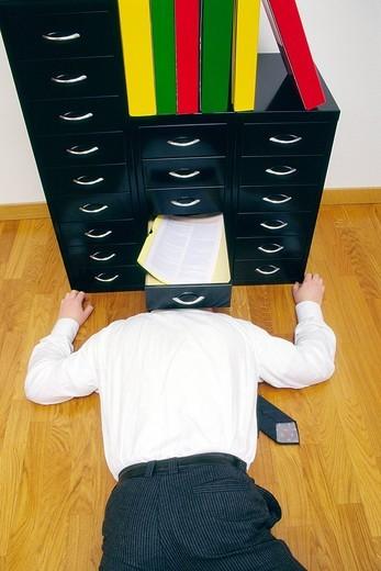 uomo in ufficio sdraiato sotto una cassettiera. man in office lying in a drawer : Stock Photo