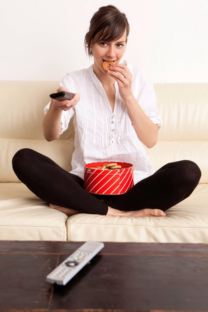 donna mangia dei biscotti guardando la tv con un telecomando in mano. Woman eating cookies while watching TV with a remote control in hand : Stock Photo