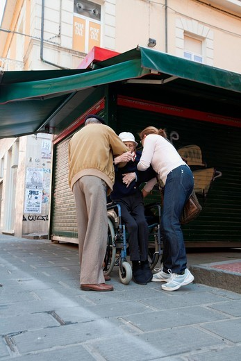 una donna invalida viene aiutata a salire sulla sedia a rotelle. invalidated woman is helped to get a wheelchair : Stock Photo