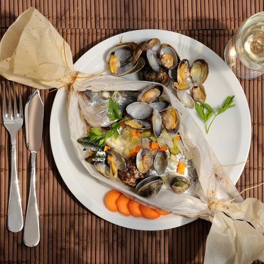 orata al cartoccio e vongole. baked sea bream and clams : Stock Photo