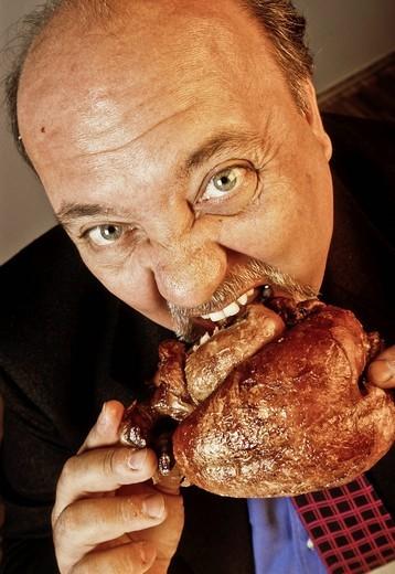 uomo mentre addenta un pollo allo spiedo. a man while eating a grilled chicken : Stock Photo