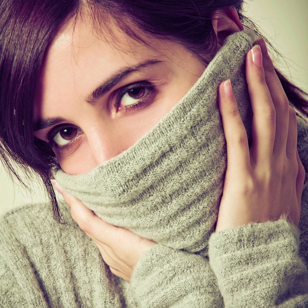 Stock Photo: 3153-851290 ragazza con maglione sul viso. young woman with sweater on the face