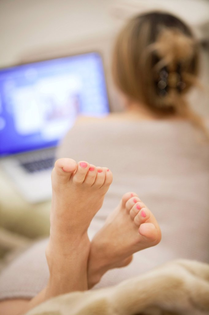 piedi di donna al computer. feet of a woman at computer : Stock Photo