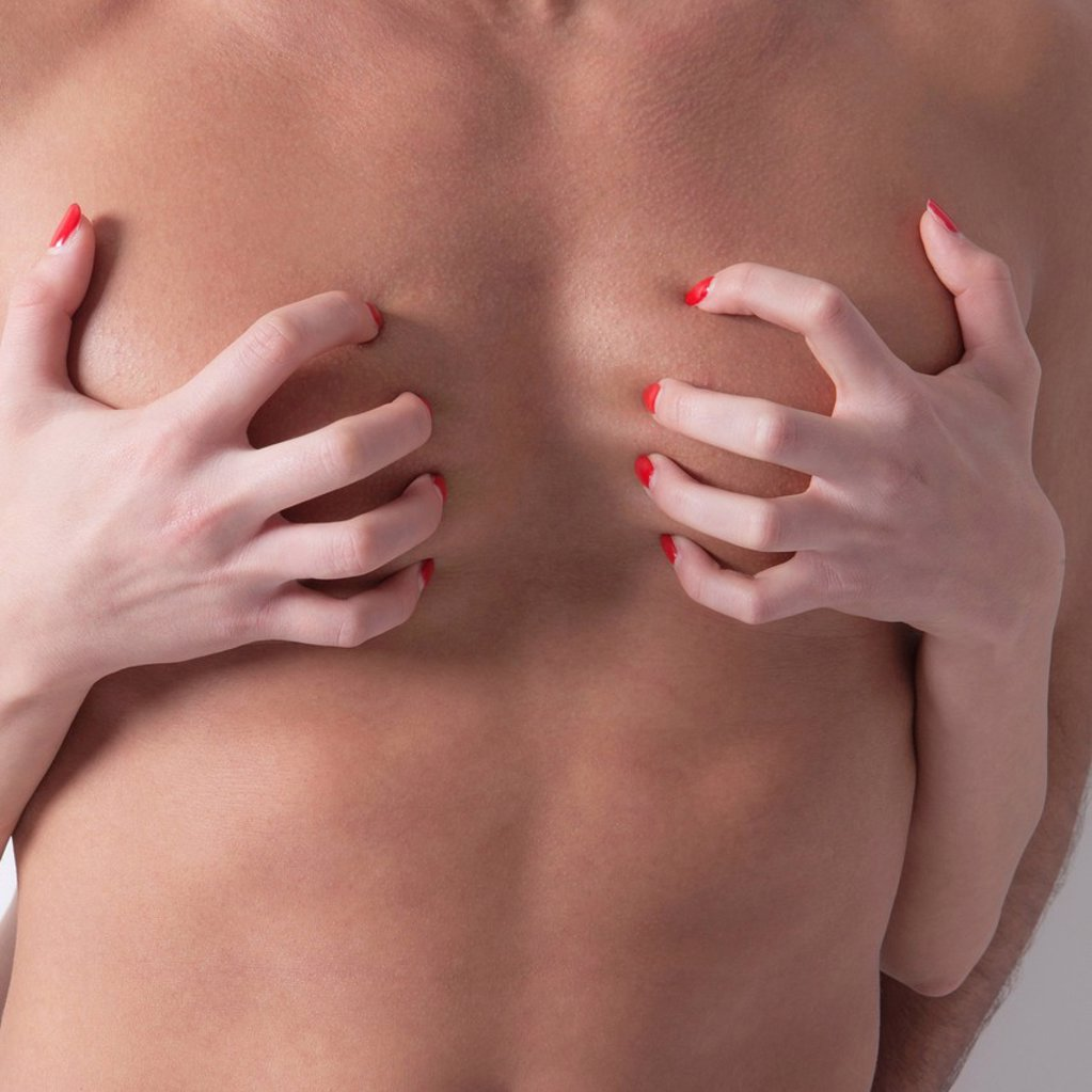 mani di una donna graffiano il petto di un uomo. hands of a woman scratching the chest of a man : Stock Photo