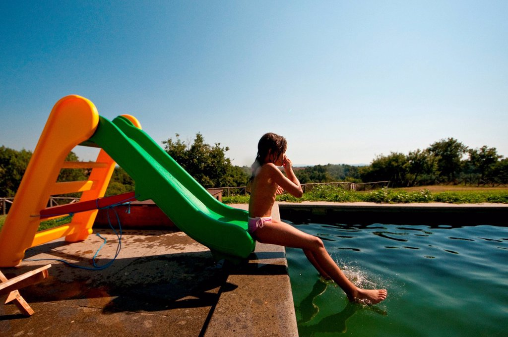 Stock Photo: 3153-854702 bambina in piscina su uno scivolo. girl in the pool on a slide