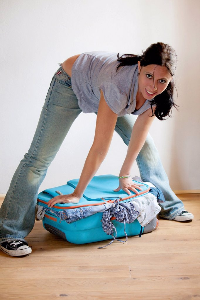 donna cerca di chiudere la valigia. woman trying to close her suitcase : Stock Photo