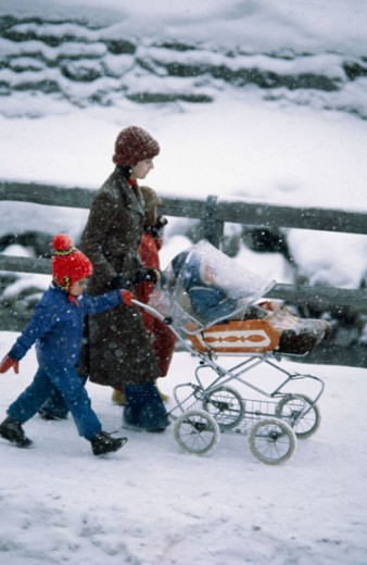 Stock Photo: 3214-578138 Side profile of a mid adult woman with her children walking on a snow covered road