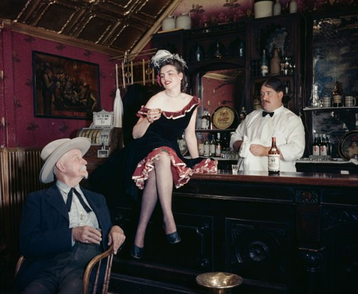 Senior man looking at a young woman sitting on a bar counter with a bartender standing behind her : Stock Photo