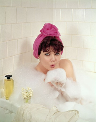 Portrait of a young woman taking a bubble bath : Stock Photo