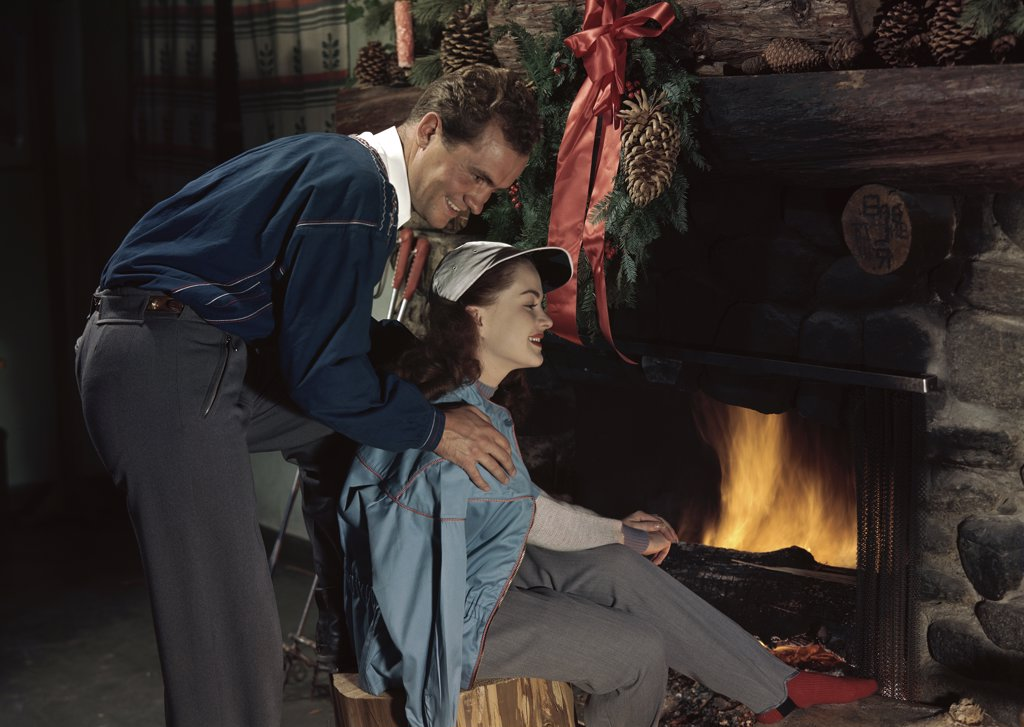 Young couple sitting near a fireplace : Stock Photo