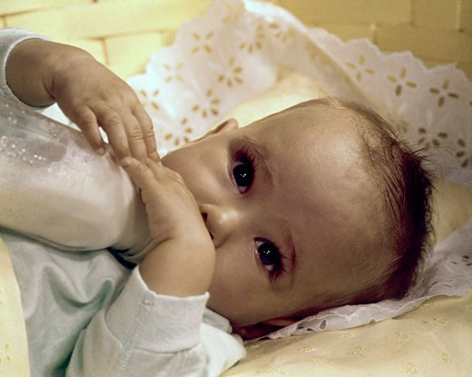 Close-up of a baby drinking milk from a baby bottle : Stock Photo