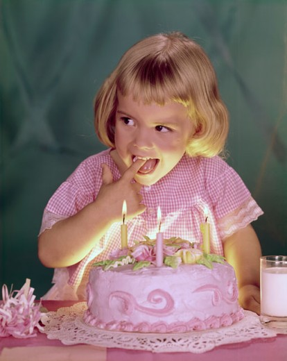 Close-up of a girl licking the icing of a birthday cake : Stock Photo
