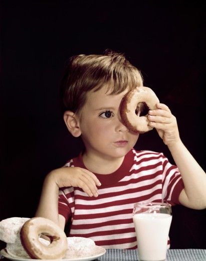 Stock Photo: 3811-360894 Close-up of a boy looking through a donut