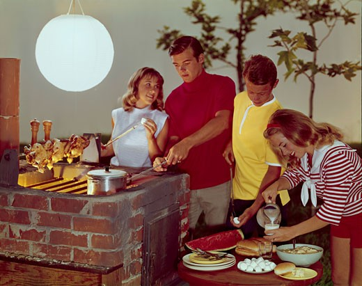 Two teenage couples preparing food on a barbecue grill : Stock Photo