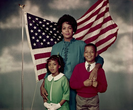 Stock Photo: 3811-361918 Portrait of a mid adult woman standing with her daughter and son in front of an American flag