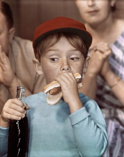 Stock Photo: 3811-361954 Close-up of a boy eating a hot dog and holding a bottle of soda