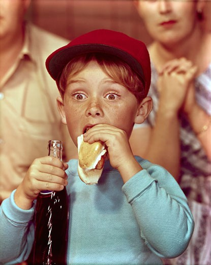 Close-up of a boy eating a hot dog and holding a bottle of soda : Stock Photo