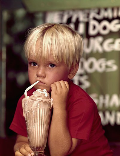 Stock Photo: 3811-362057 Close-up of a boy drinking an ice cream float with a drinking straw