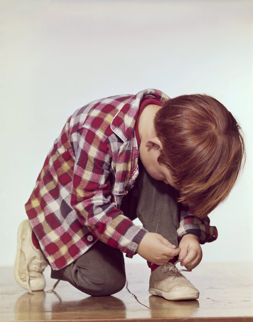 Stock Photo: 3811-362264 Close-up of a boy tying his shoelaces