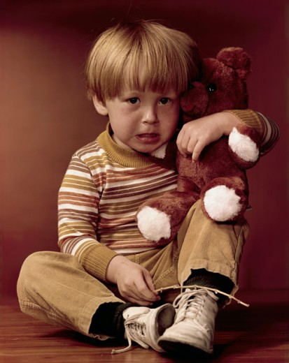 Stock Photo: 3811-362903 Portrait of a boy holding a teddy bear and looking displeased