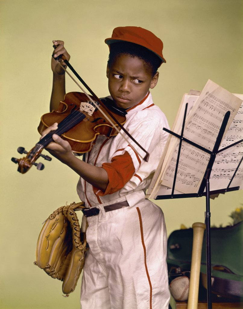 Close-up of a boy looking at a musical stand and playing a violin : Stock Photo
