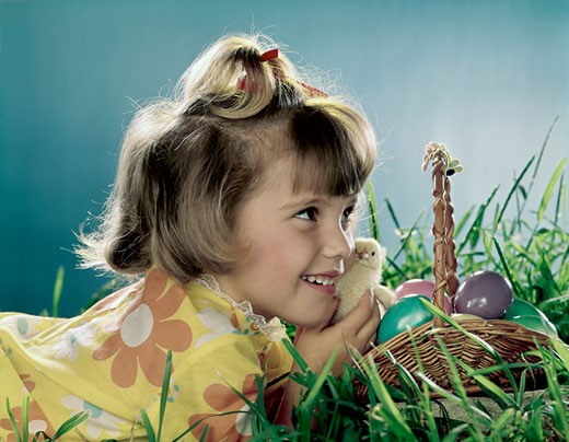 Close-up of a girl holding a chick and smiling : Stock Photo