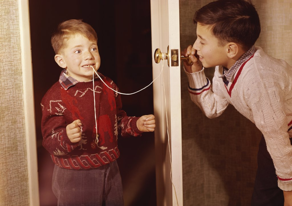 Stock Photo: 3816-349487 Boy attempting to extract his brother's loose tooth using string and doorknob technique