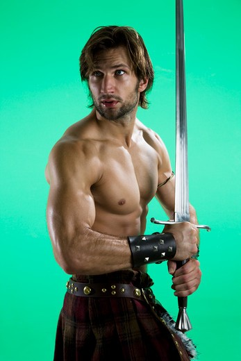 Young man in warrior costume holding a sword : Stock Photo