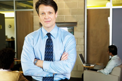 Portrait of a businessman standing with his arms crossed : Stock Photo