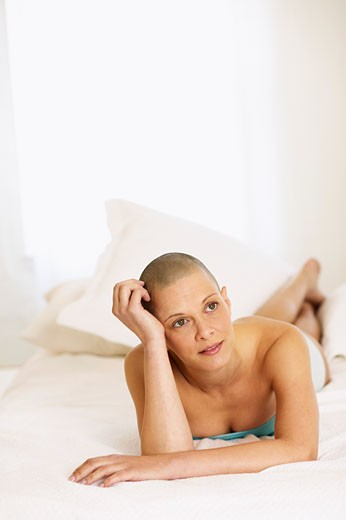 Stock Photo: 4001-331 Shaved head young woman lying on the bed