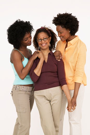 Mature woman smiling with her daughters : Stock Photo