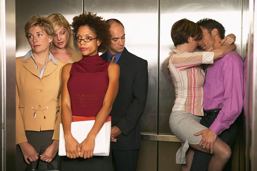 Couple romancing in an elevator and business executives standing beside them : Stock Photo