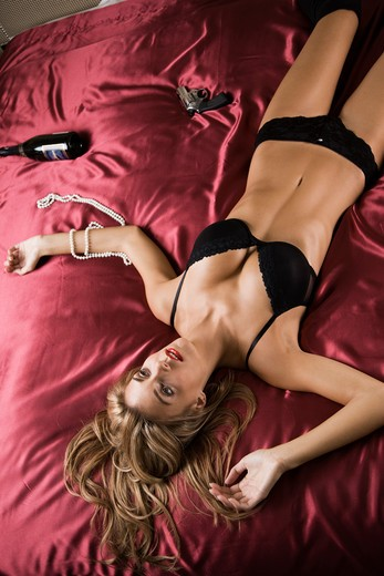 Stock Photo: 4001-758 Woman lying on the bed with a handgun and a wine bottle