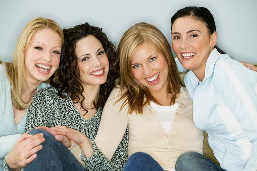 Four young women sitting together and smiling : Stock Photo