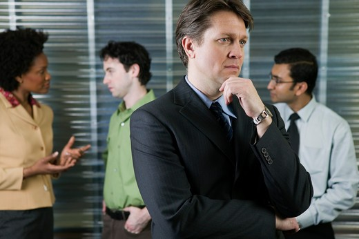 Stock Photo: 4001-903 Businessman thinking while meeting goes on in the background