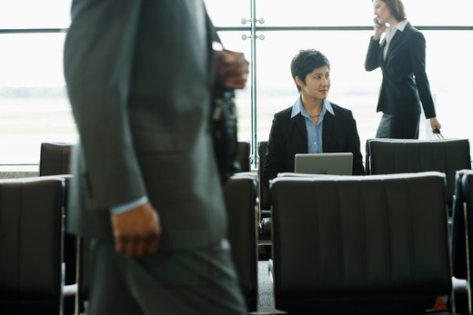 Stock Photo: 4001-994 Businesswoman checking in at automated airport ticket counter
