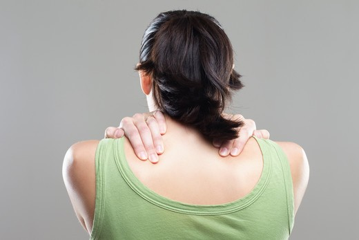 Rear view of a young woman suffering from neckache : Stock Photo