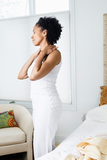 Mid adult woman standing in the bedroom and suffering from backache : Stock Photo