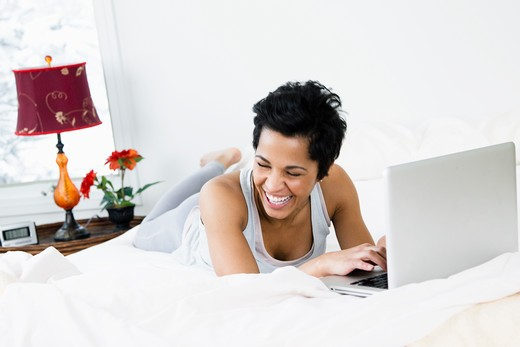 Mid adult woman using a laptop on the bed : Stock Photo