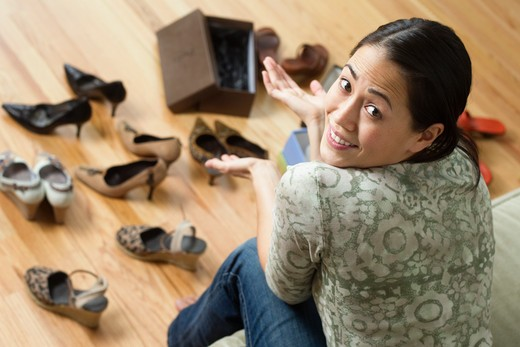 Stock Photo: 4001R-1386 Young woman deciding which shoes to wear