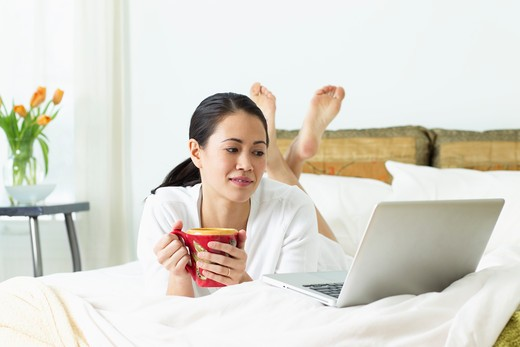 Young woman drinking coffee on the bed and looking at a laptop : Stock Photo