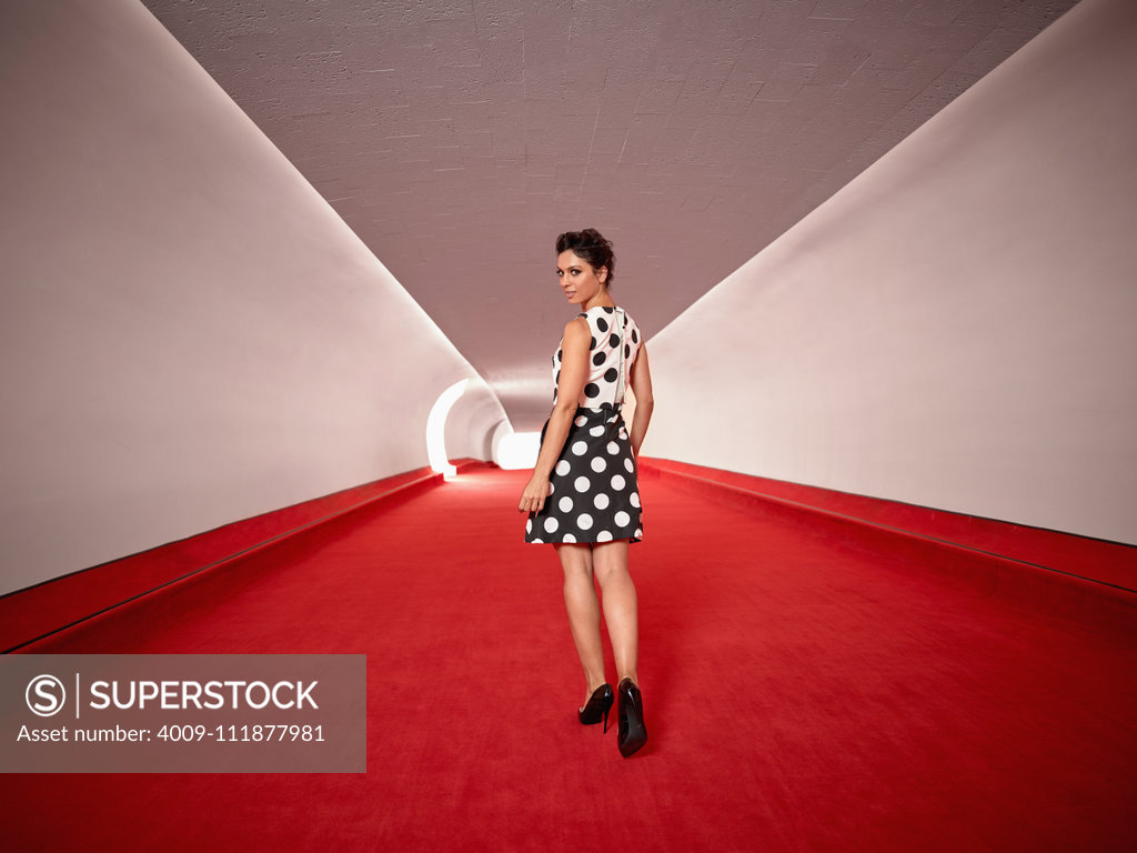 Stock Photo: 4009-111877981 Full length portrait of a woman walking down a hallway with red carpet at the TWA hotel designed by Eero Saarinen at JFK Airport