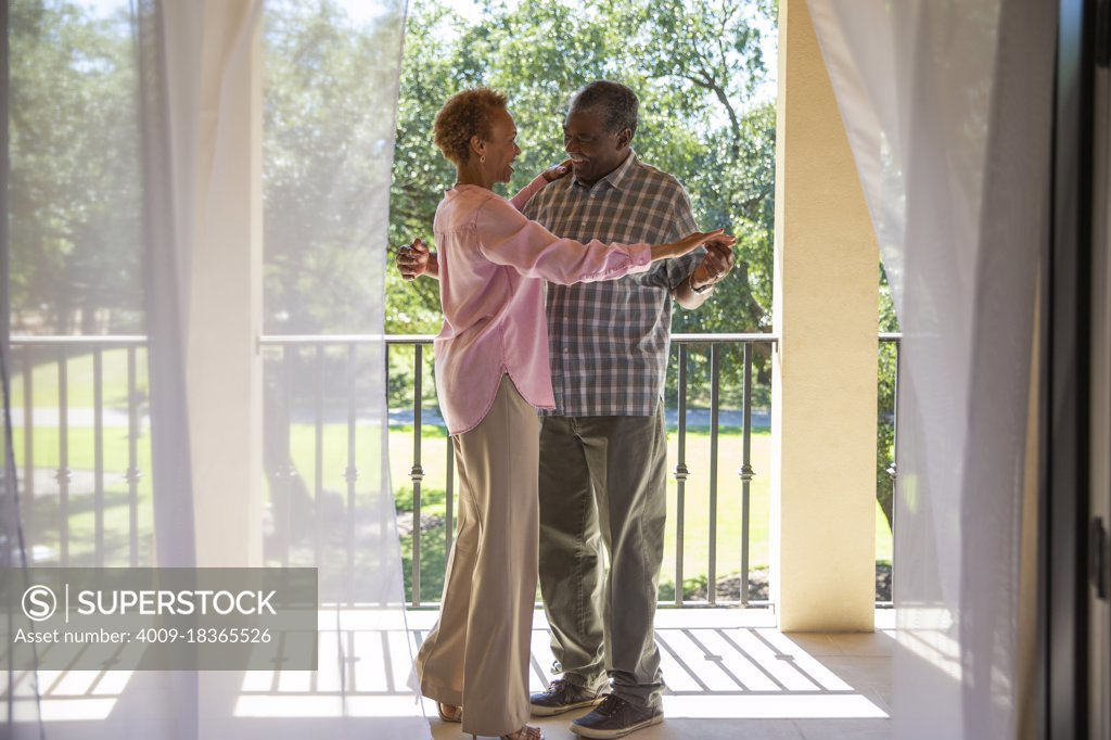 Stock Photo: 4009-18365526 Older couple dancing on porch overlooking  green lawn , seen through sheer curtains