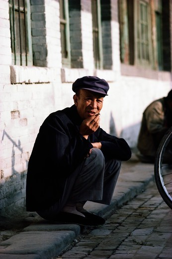 Stock Photo: 4009-1083 Man smoking a cigarette while squatting on the sidewalk, China