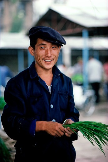 Stock Photo: 4009-1125 Portrait of a man holding a bunch of chives, China