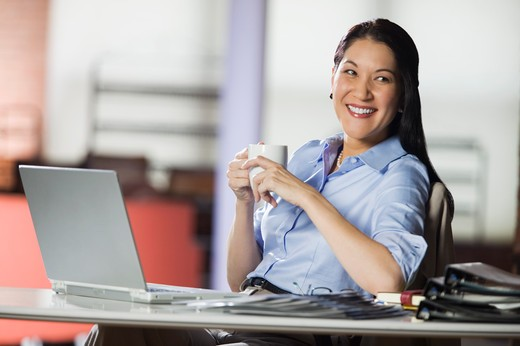 Stock Photo: 4009-244B Businesswoman sitting at desk holding a cup of coffee