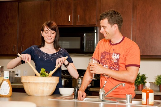 Couple preparing dinner in a kitchen : Stock Photo