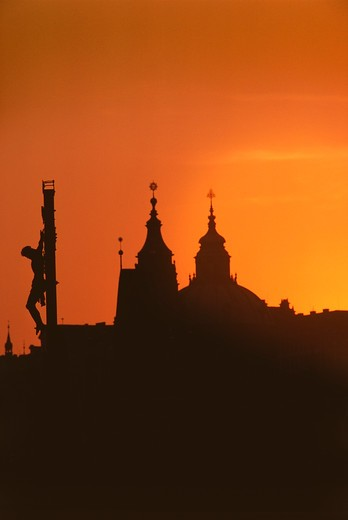 Stock Photo: 4009-580 Silhouette of statue of Jesus Christ and a cathedral at sunset, Charles Bridge, Prague, Czech Republic