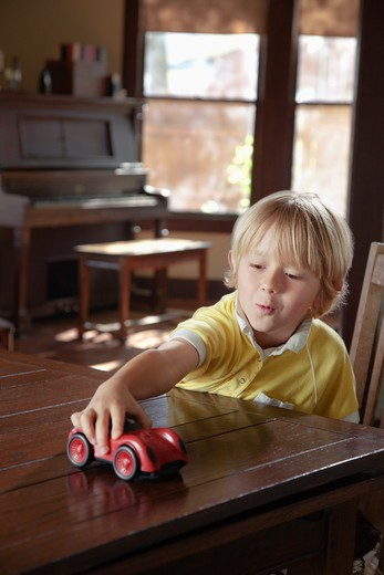 Stock Photo: 4009-763 Boy playing with toy car on a table