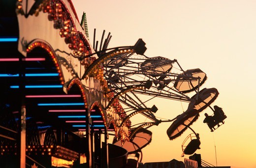 Stock Photo: 4009-815 People riding a carnival way ride at sunset at the the Texas State Fair, Dallas, Texas, USA